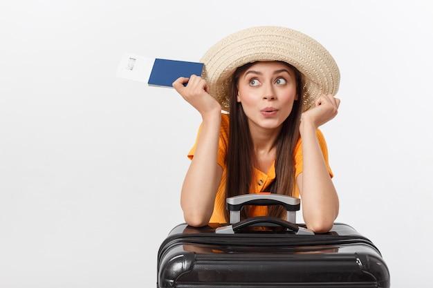 旅行のコンセプト。パスポートと荷物を保持しているかなり若い女性のスタジオポートレート。白で隔離