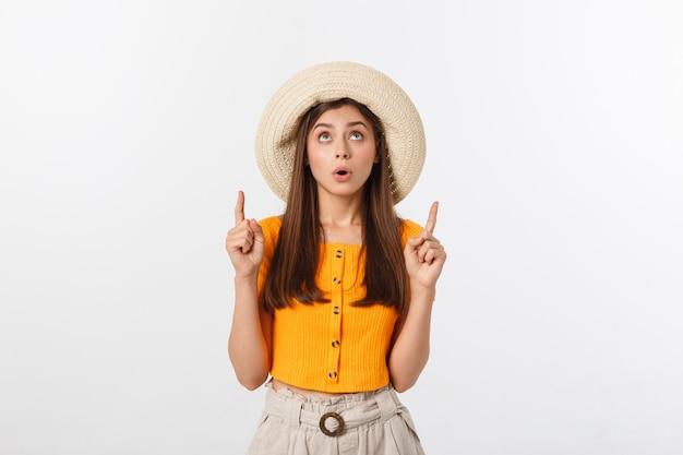夏休みのティーンエイジャーの女の子は驚いて、孤立した白でコピースペースに指を指しています。