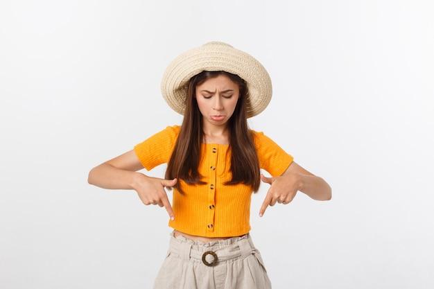 Молодая милая женщина смотря несчастный и усиленный, жест самоубийства делая знак оружия с рукой, указывая к космосу экземпляра.