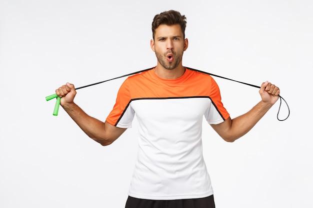 ハンサムで活気のあるスポーツマンのトレーニングの準備ができて、首の後ろに縄跳びを保持し、生意気な顔をしかめ