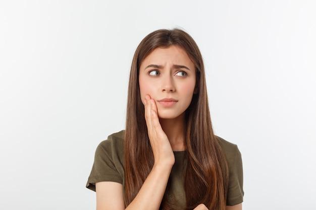 Подростковая женщина с болезненным выражением нажимает на ушибленную щеку, как будто у нее ужасная зубная боль