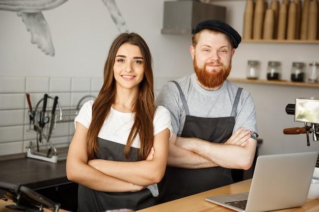 Концепция кофе бизнес - положительный молодой бородатый мужчина и красивая привлекательная пара бариста леди в фартуке, глядя на камеру, стоя в баре. кутер готов дать кофе в современной кафе.