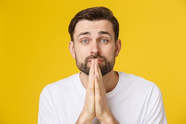 Молодой парень, одетый небрежно изолирован на желтом фоне, сложив руки в молитве или медитации, выглядит расслабленным и спокойным.
