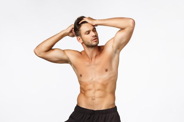 ボディービル、自信、スポーツコンセプト。ハンサムなセクシーな若い男性