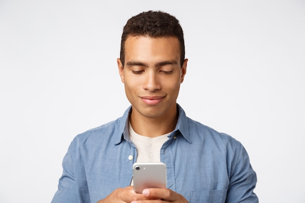 カジュアルな服装でハンサムなスタイリッシュなモダンなヒスパニック男、スマートフォンを保持、ガールフレンドへのメッセージを入力して笑顔