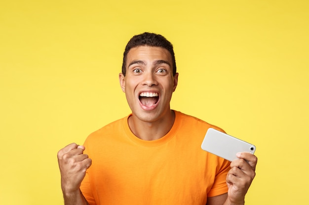 ハンサムな陽気な男がモバイルゲームで優勝し、スマートフォンを横に持ち、賞を獲得し、応援からレベルと拳ポンプを獲得しました