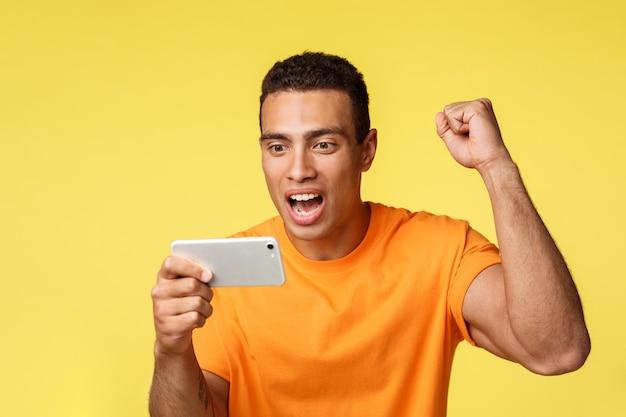 Радостный возбужденный молодой красавец в оранжевой футболке, поднять руку вверх кулаком насоса, как болеть за любимую команду, горизонтально держать смартфон, смотреть футбол на мобильном устройстве, желтый фон