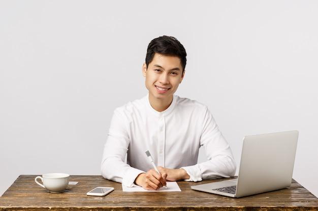 Успешный жизнерадостный азиатский мужской предприниматель сидя офисный стол с ноутбуком, смартфон пить кофе, работая, чтобы разбогатеть, успешный, улыбаясь как смотреть камеру, писать заметки, отчет,