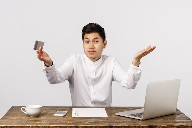 何を買うべきか分からない。ラップトップ、ドキュメント、クレジットカードを持っているオフィスの近くに座っている困惑した、自信がない、混乱している中国人男性、オンラインで注文を決定しようと肩をすくめ、
