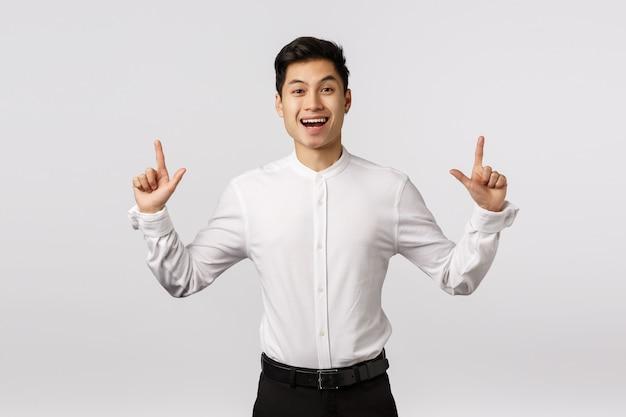 Жизнерадостный милый азиатский парень празднуя дня рождения приглашая гостей видит фейерверк. человек радуется, как стоит в костюме, смотрит вверх, улыбается и развлекается, находит понравившийся ему товар,