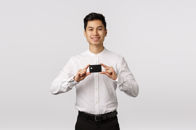 ビジネスマンは、新しいクレジットカードを取得しました。銀行カードを保持し、喜んで笑って、キャッシュバックで支払い、ボーナスを得て、金融商品を紹介して、見栄えの良いアジアの若い男、