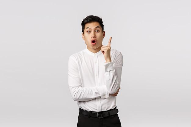 興奮し、魅了されたアジア系ビジネスマンが解決策を見つけ、優れたアイデアを得て、ユーレカで人差し指を上げ、ジェスチャーをして、口を開けて、彼の提案を言って、興奮して立っている