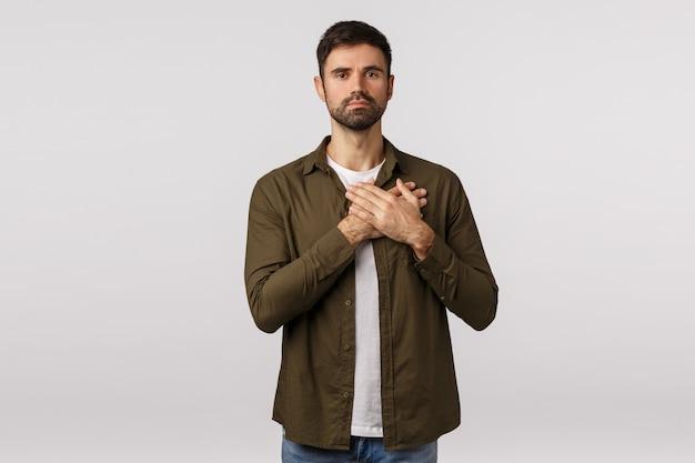 Преданный и мужественный, преданный молодой бородатый мужчина, прижимающий руки к сердцу и смотрящий в камеру, выражающий верность и веру, слушающий государственный гимн, чувствуя себя тронутым или тронутым,