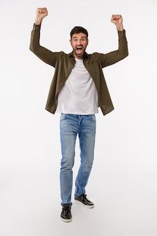 Концепция успеха, достижения и победы. вертикальный полноразмерный снимок радостного и счастливого торжествующего юного бородатого мужчины в джинсах и пальто, поднять руки вверх в ура, победный жест, празднование отличных новостей