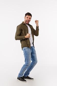 達成、目標、勝利のコンセプト。完全な長さの垂直ショットカジュアルな衣装で陽気なハンサムな成功した実業家、勝利を祝って、勝利を祝って、チャンピオン、拳ポンプになります