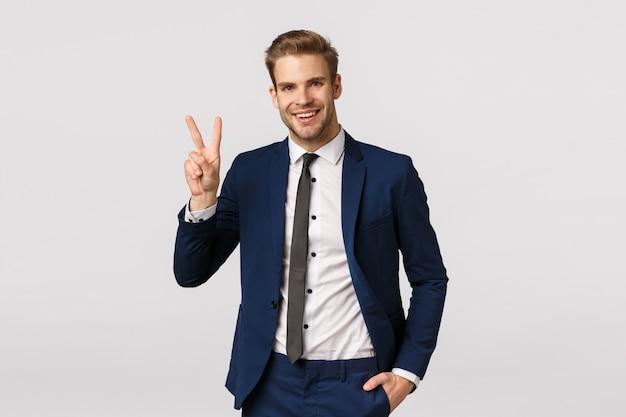 Очаровательный, богатый, красивый бородатый парень в классическом костюме, показывая знак мира, радостно улыбаясь, рассказывая команде, что они заключили сделку, бизнесмен рад, как хорошее предложение пошло, белый фон