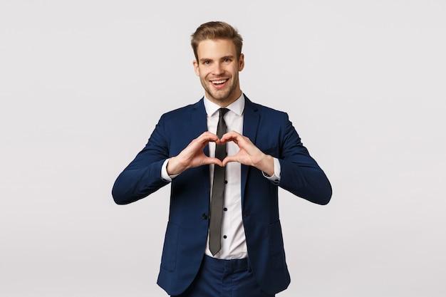 Радостный бородатый молодой белокурый мужчина в синем классическом костюме, показывая знак сердца и улыбаясь, приходят из офиса домой, готовят сюрприз для подруги, поздравляют с днем святого валентина, на белом фоне