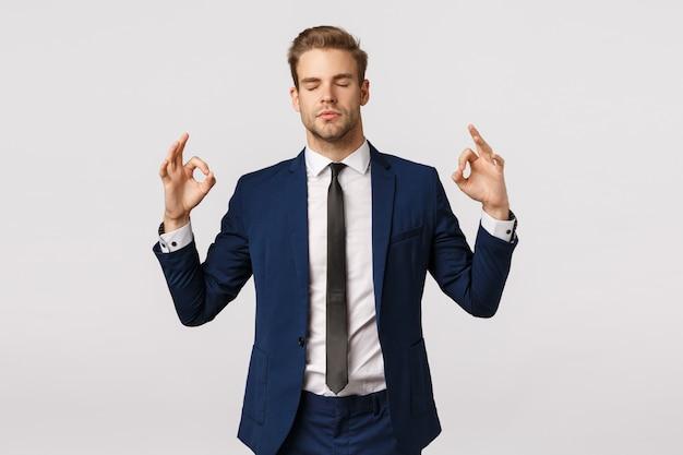 Не паникуйте, взяв эмоции под контроль. спокойный и терпеливый красивый белокурый бизнесмен в классическом костюме, делает знак дзен, разводит руками в стороны, закрывает глаза, медитирует, снимает стресс