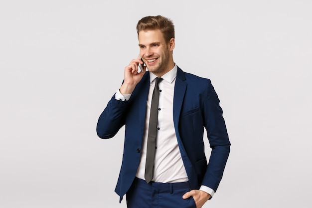 Привлекательный, успешный и богатый молодой кавказский бизнесмен в костюме, говорить по телефону, держа смартфон возле уха, вызывая иностранных партнеров по бизнесу, обсудить корпоративный персонал, белый фон