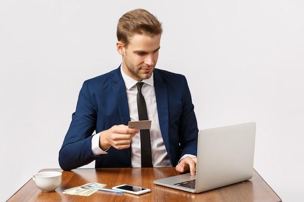 ビジネス、起業家、仕事のコンセプト。オフィスに座っている古典的なスーツのハンサムな男性は、ガールフレンドを驚かせたい、オンラインショップで注文、クレジットカードを保持、ラップトップで銀行番号を挿入したい