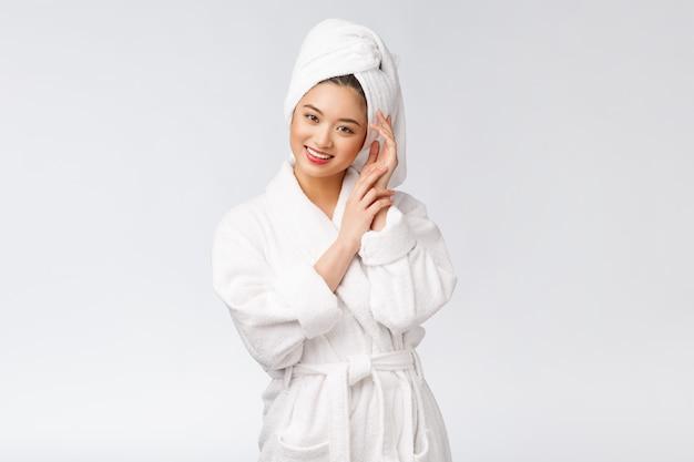 Портрет молодой счастливой азиатской дамы в купальном халате. изолированный в белой предпосылке.