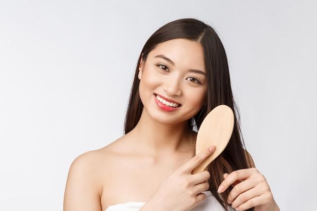 Портрет красивой молодой женщины, расчесывать прекрасные волосы, изолированные на белом фоне, азиатские красоты