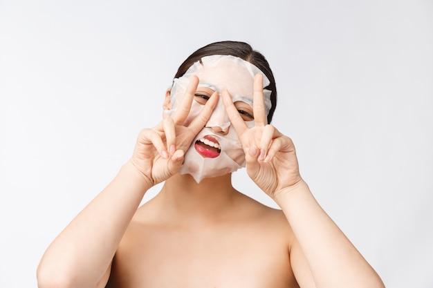 Спа, здравоохранение. женщина с очищающей маской на лице, изолированные на белом фоне.