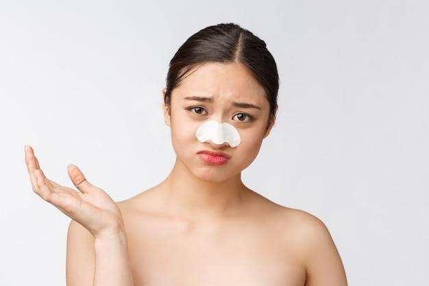 美容。鼻にマスクを持つ美しい女性アジアモデルの肖像画。純粋な柔らかい肌と新鮮なナチュラルメイクで健康な若い女性のクローズアップ。