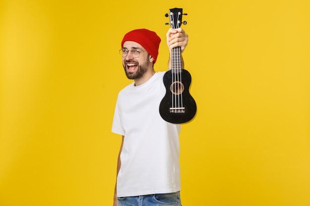Крупным планом смешной молодой человек играет на гитаре. изолированные на желтом золоте