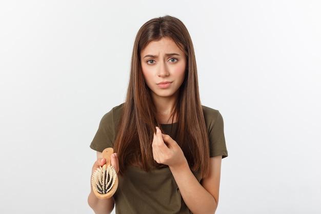 クローズアップ不幸な欲求不満の若い女性は彼女が髪を失って驚いた、分割終了ヘアラインを後退に気づいた。灰色の背景