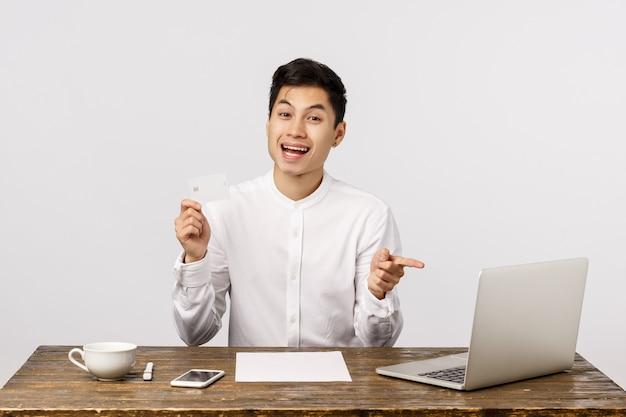 金融、ショッピングのコンセプト。ハンサムなアジアの若い男がオフィスの机に座って、ラップトップのディスプレイ、アドバイスオンラインサイト、銀行システム、預金の選択肢を指しているクレジットカードを保持