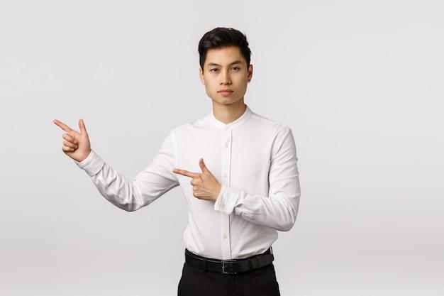 真面目なアジア系のビジネスマンは、左を指している方向を与える