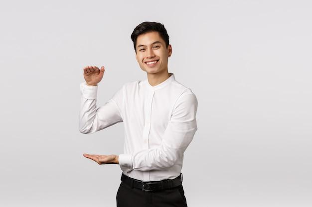 うれしそうな格好良いアジアの男性起業家、白いシャツ、パンツの従業員、満足のいく表情で大きな箱を見せ、製品や何かを大きく満足させるものを保持