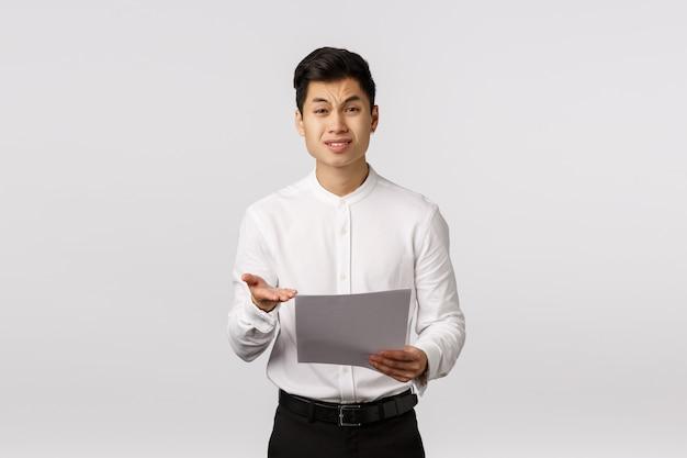 これは何ですか。不愉快な懐疑的で感銘を受けない偉そうなアジア系のビジネスマンは、従業員が悪い報告をし、書類を持ち、書類を指差し、嫌悪感、不承認を訴えた