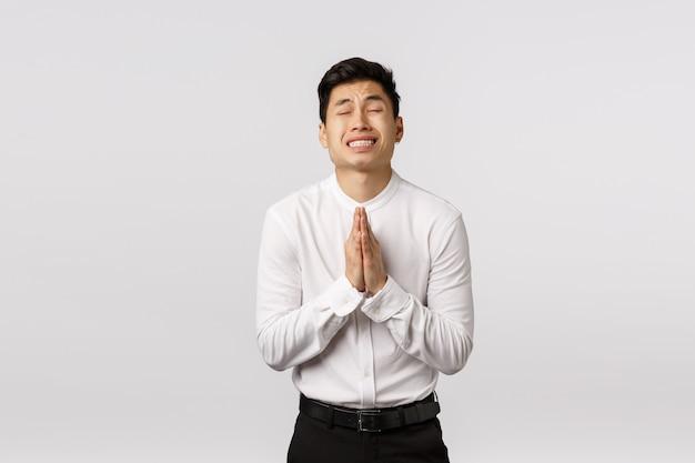 Обеспокоенный, обнадеживающий молодой азиатский предприниматель мужского пола, бизнесмен, молящийся, умоляющий босса, дает ему второй шанс, закрывает глаза, нервно молит зубы