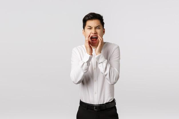 大声でのろいの言葉を宣誓し、叫ぶ男。怒っている、怒り、不快なアジア人は、メガホンのような開いた口の近くで手をつないで、議論や戦いをしている人に叫ぶ
