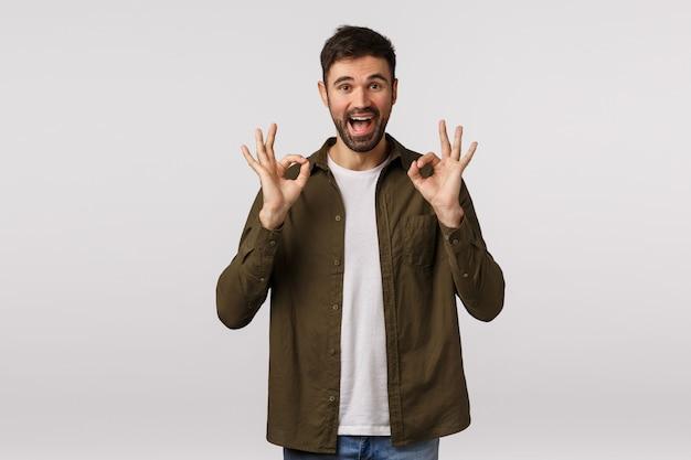 Интервью прошло хорошо, было отлично. довольный уверенный и оптимистичный современный бородатый парень показывает хорошо, одобрение или хорошо знаком обеими руками, улыбается довольный, абсолютно влюблен, обожаю продукт, рекомендую