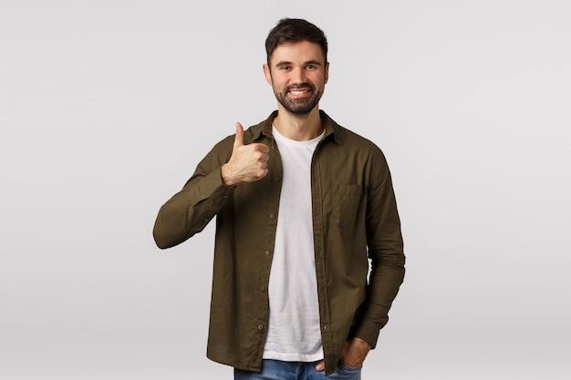 カジュアルなコートを着た陽気なフレンドリーなひげを生やした男性、親指を立てて笑顔を見せ、許可を与え、計画を承認し、同意するなど、会社のサービスをお勧めします