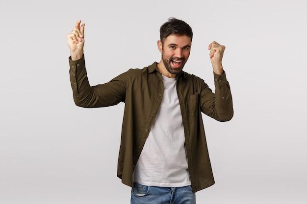 Концепция празднования, триумфа и радости. счастливый веселый кавказский мужчина с бородой, поднимающий руки и счастливо танцующий, достигает цели, получил одобрение или нанял отличную работу, стал чемпионом, побеждая
