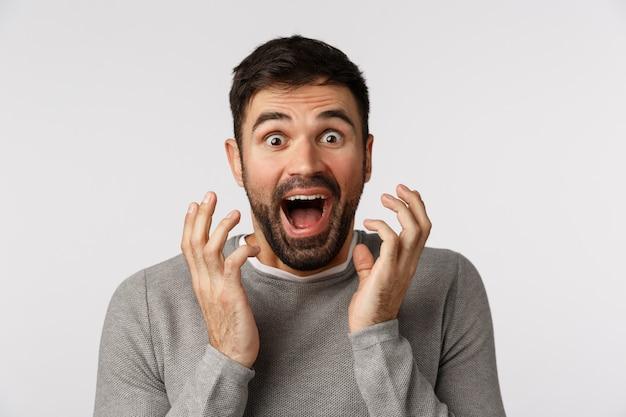 灰色のセーターを着た、興奮した陽気で明るい格好のひげを生やした男、驚くべきニュースを聞き、顔の近くで握手し、驚いた叫び、勝利し、賞を受け取り、目標を達成する