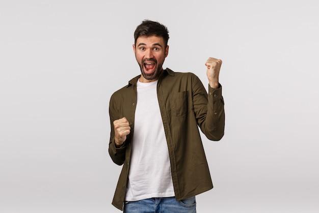 Смак, праздник и победа концепции. веселый победоносный счастливчик, парень, побеждающий, достигший приза или цели, отличные новости, кулак и улыбка, становящийся чемпионом