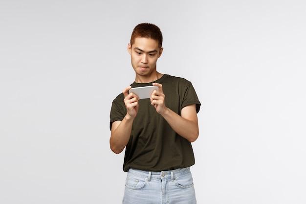 興奮した若い男が分離された彼のスマートフォンでゲームをプレイ