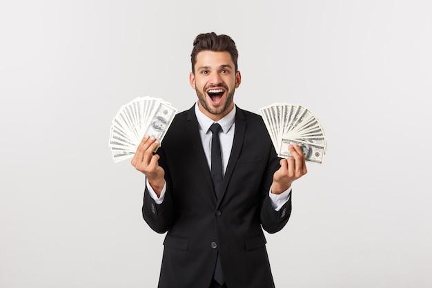Портрет удовлетворенного молодого бизнесмена держа кучу банкнот денег изолированный