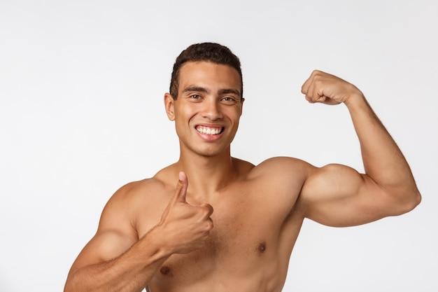 Афро-американский подросток показывает мышцы на руке. изолированные.