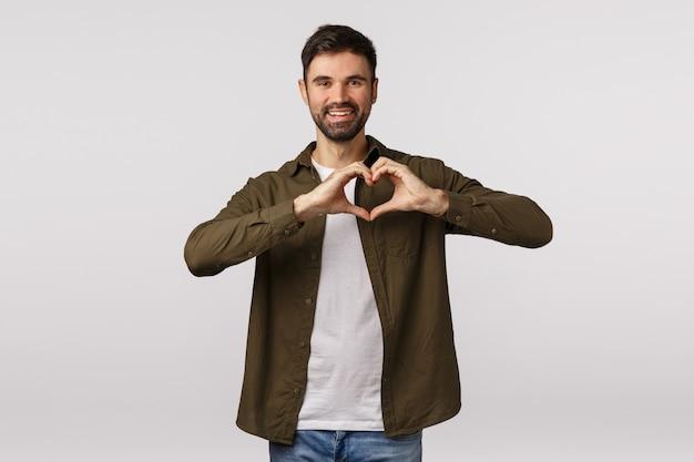День святого валентина, любовь и отношения концепции. веселый нежный бородатый мужчина в пальто, показывающий сердечный жест возле груди, выражающий любовь или украшение, милый улыбающийся, выражающий благодарность или привязанность