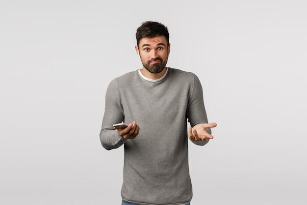 不確かで無知で、灰色のセーターを着た困惑したハンサムなひげを生やした男性、不確かな感じ、にやにや笑い、知らずに肩をすくめ、横に手を上げ、スマートフォンを持ち、ワイヤレスイヤホンを着用する