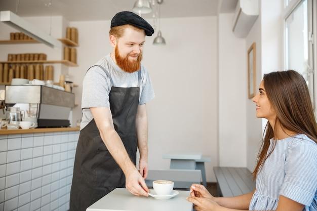 コーヒービジネスのコンセプト - コーヒーショップで青いドレスで白人の美しい女性と話し、熱いコーヒーを提供するウェイターまたはバーテンダー。