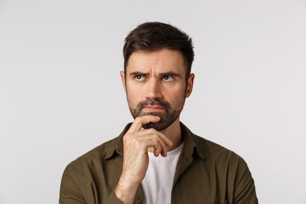 コートの若い男、あごに触れると思慮深く離れて見て眉をひそめ、考えて、何をするかを検討、選択、熟考計画、ソリューションを検索