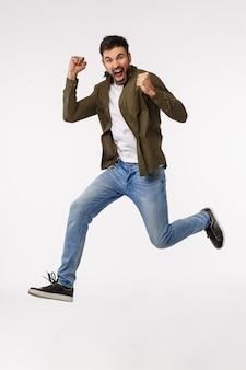 Достижения, поздравления и бизнес-концепция. привлекательный веселый человек прыгает от триумфа и праздника, достигает цели, выигрывает приз, сжимает руки доволен
