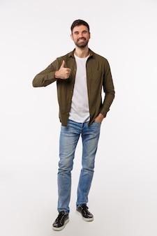 承認、受け入れ、アドバイスのコンセプト。ジーンズ、薄手のコート、魅力的なモダンな男性的なひげを生やした男、ジェスチャーのように親指を表示、製品をお勧め、アイデアを愛する